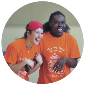 A candid photo of two teens laughing during Beep Ball. They are both wearing orange tshirts with the event logo on it.