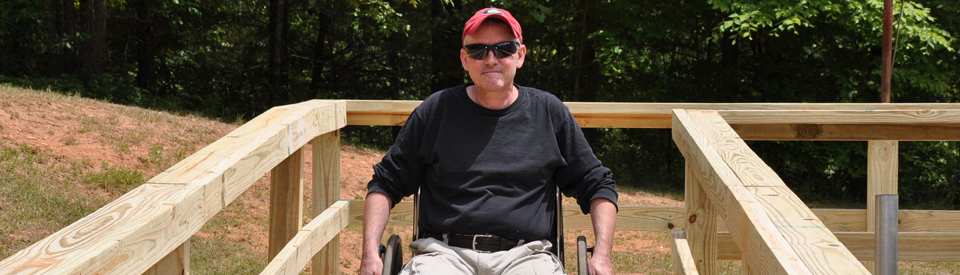 A man in a wheelchair, sunglasses and baseball cap rolls down a newly built home ramp.