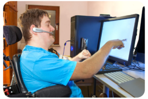 A man sitting in his wheelchair is pointing at a computer screen on his desk. He appears to be speaking into the headset positioned on his ear.