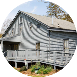 Circle Photo: the outside of a house with grey siding. The focus of the photo is the accessible ramp running along the side of the house.
