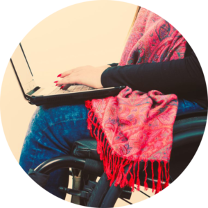 Circle photo: a person using a laptop while sitting in her wheelchair. The focu of the photo is the laptop and the hands using the laptop.